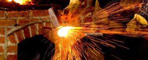 Site logo - a blacksmith strikes hot metal on an anvil, sending sparks and welding flux flying